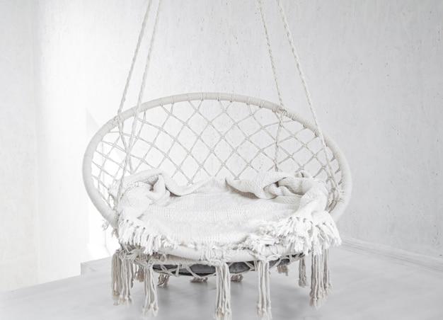 Scena hygge z białym fotelem hamakowym z szarą poduszką na białej ścianie. przytulne miejsce na weekendowy relaks w pokoju.