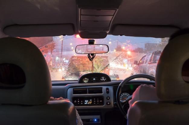 Scena jazdy w ulewny dzień i korki w pięknym świetle jasnym w nocy