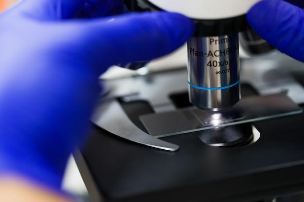 Scena laboratorium medycznego, naukowiec ręce przy użyciu mikroskopu do próbek chemii w laboratorium