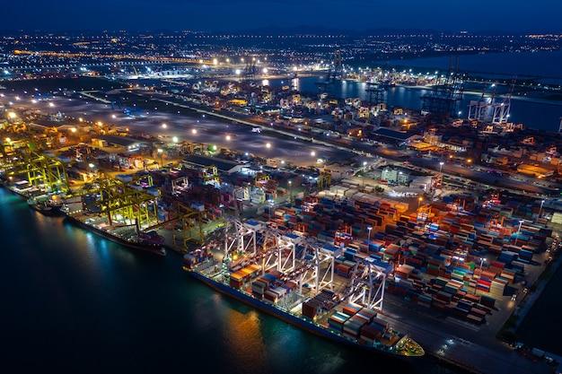 Scena nocna załadunek i rozładunek kontenerowca w porcie dalekomorskim, widok z lotu ptaka usług biznesowych i logistyki ładunków przemysłowych, import i eksport towarów transportem kontenerowym na otwartym morzu,