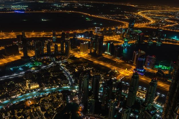 Scena nocy w centrum dubaju ze światłami miasta. widok z góry z góry