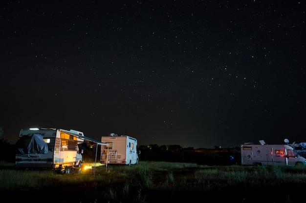 Scena nocy z kamperem kamperów na kempingu