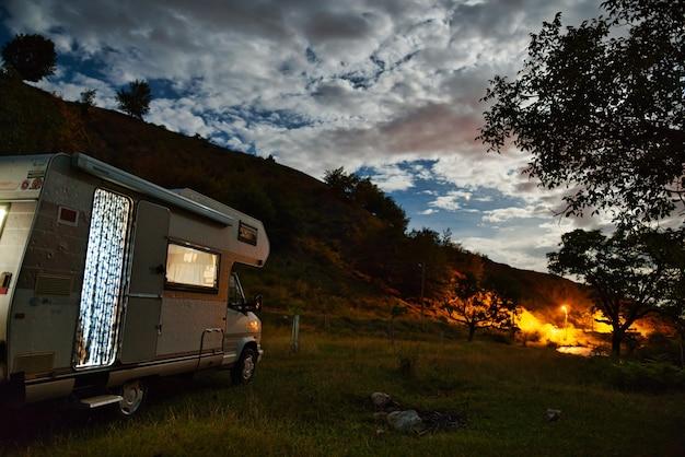 Scena nocy z kamperem w przyrodzie