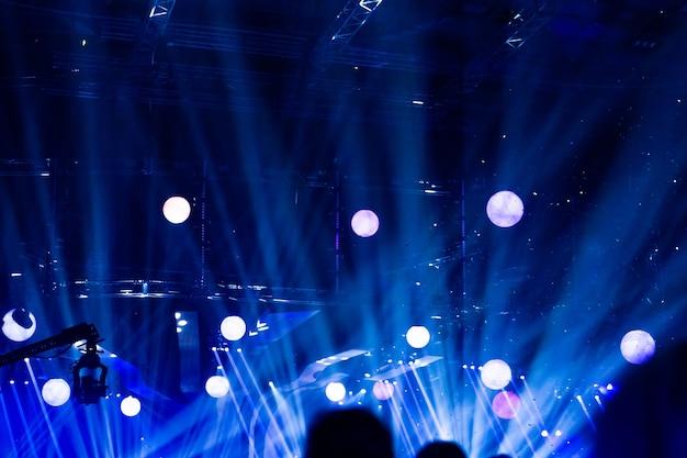 Scena, oświetlenie koncertowe. nowoczesne wyposażenie reflektorów. przez dym prześwitują piękne wielobarwne promienie.
