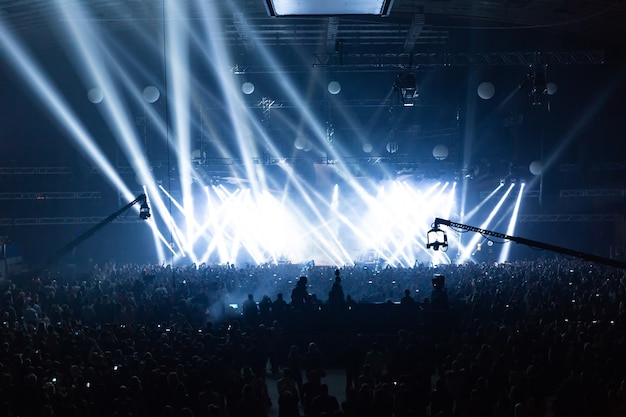 Scena oświetlona pięknymi promieniami sprzętu oświetleniowego. tłum koncertowy bawi się na środku w dużej sali.
