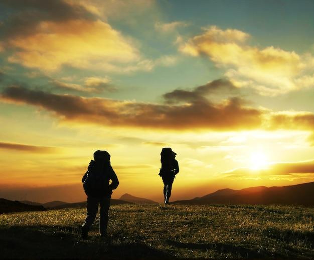 Scena pieszych wycieczek w piękne letnie góry o zachodzie słońca