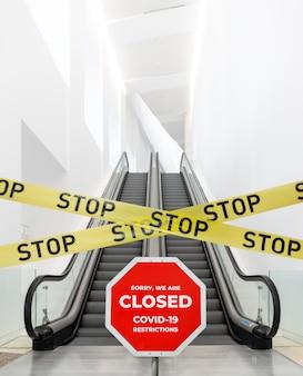 Scena publiczny kryty taśmą barierową i znak stop. zamknięty budynek podczas epidemii koronawirusa covid-19