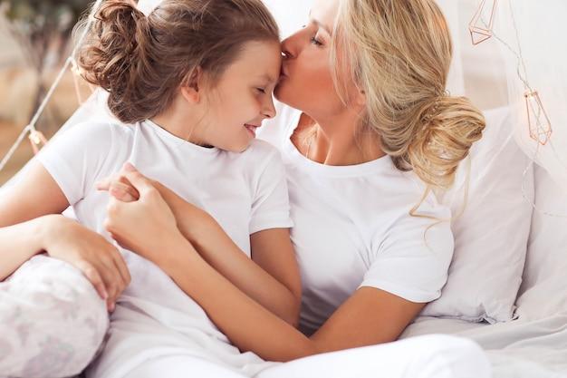Scena rodzinna. szczęśliwa matka i córka w łóżku