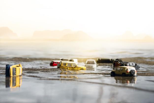 Scena samochodów (miniatura, model zabawki) w powodzi po klęskach żywiołowych, ulewny deszcz, tajfun, huragan. transport, koncepcja ubezpieczenia samochodu