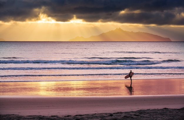 Scena surfingowa na wybrzeżu nowej zelandii, czas wschodu słońca