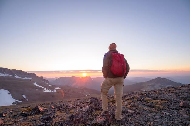 Scena wędrówek w pięknych letnich górach o zachodzie słońca