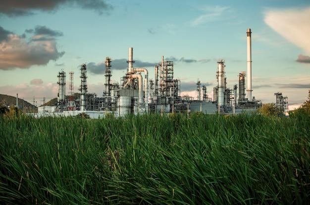 Scena wieczór wieży rafinerii oleju i kolumny zbiornika oleju przemysłu petrochemicznego błękitne niebo i trawnik