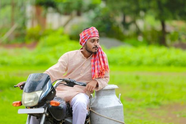 Scena wiejska: indyjski mleczarz rozdaje mleko na rowerze
