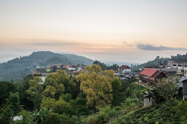 Scena wschodu słońca ze szczytem gór, chmur i krajobrazu miasta