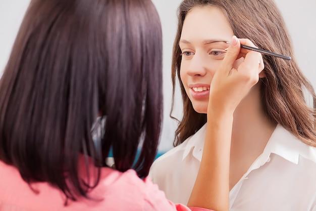 Scena za kulisami: visagiste w pracy robi makijaż modelki glamour.