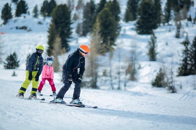Scena zimowa: grupa dzieci uczy się jeździć na nartach