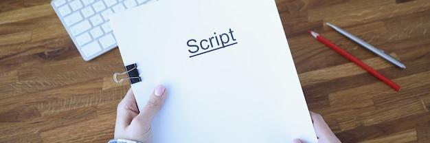 Scenarzysta trzyma teczkę z dokumentami z napisem opracowanie scenariusza fabuły do filmów i seriali