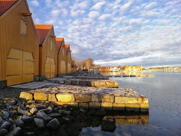 Sceneria budynków wokół jeziora pod zachmurzonym niebem w stavern w norwegii