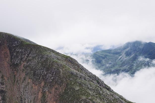 Sceneria dymu wydobywającego się z gór pośrodku zielonego widoku
