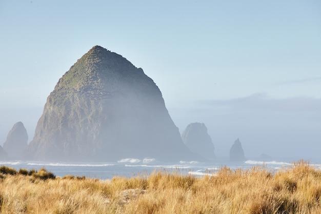 Sceneria haystack rock w porannej mgle w cannon beach w stanie oregon