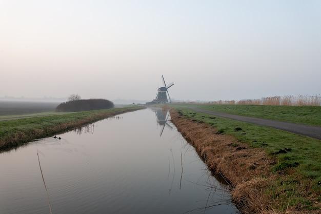 Sceneria jeziora pośrodku pokrytego mgłą pola w holandii