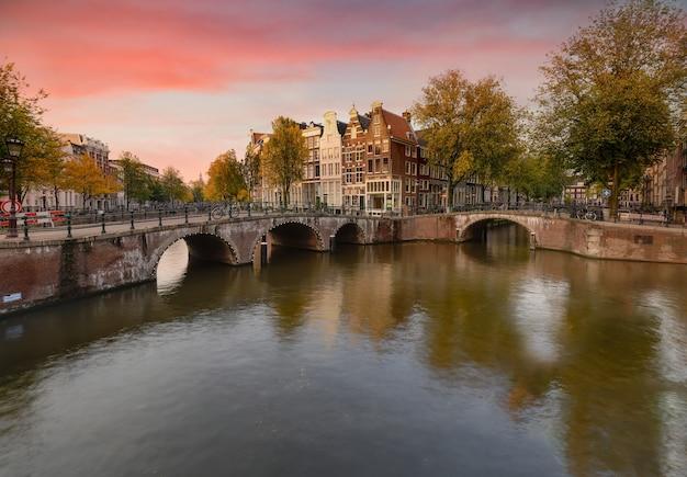 Sceneria kanału keizersgracht w amsterdamie z odbiciami budynków i zielonych drzew