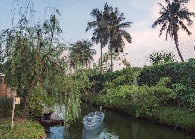 Sceneria wiejskiego ogrodu z przeźroczystą łodzią przy drewnianym molo na kanale w godzinach wieczornych