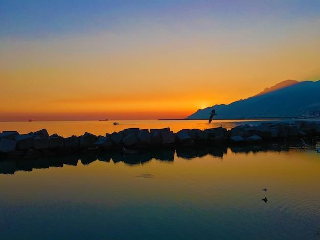 Sceneria wschodu słońca nad brzegiem morza z górami sylwetka