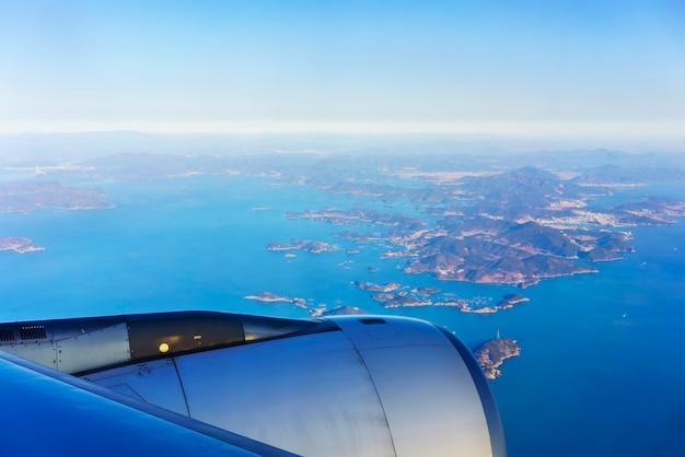 Sceneria z okna samolotu z widokiem na błękitne niebo i półwysep południowokoreański oraz przyległe wyspy o poranku