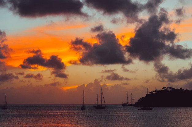 Sceneria zachodu słońca z sylwetką góry i łodzi na morzu
