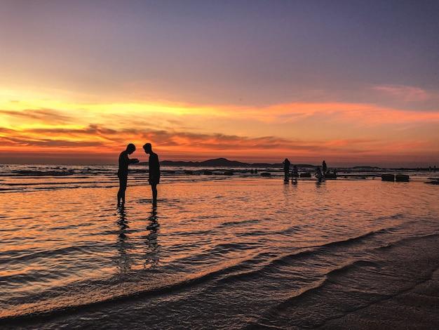 Sceneria zachodu słońca z sylwetkami ludzi na plaży