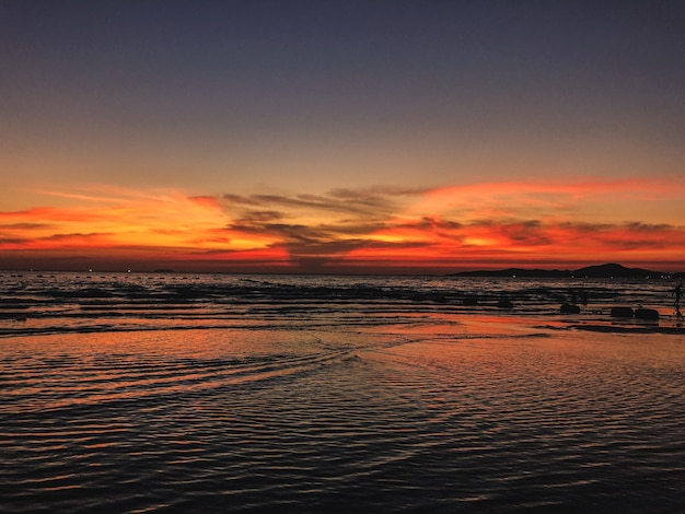 Sceneria zachodzącego słońca na plaży z uspokajającymi falami oceanu