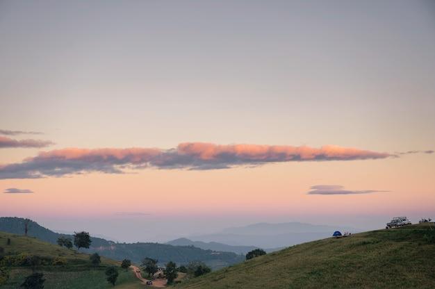 Sceneria zielonego wzgórza z kolorowym niebem i namiotem turystycznym wieczorem w parku narodowym
