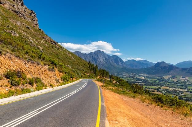 Sceniczna droga przy franschhoek doliną z swój sławnymi wytwórniami win i otaczającymi górami, południowa afryka