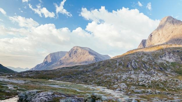 Sceniczny widok skalistej góry krajobraz z niebieskim niebem i chmurą