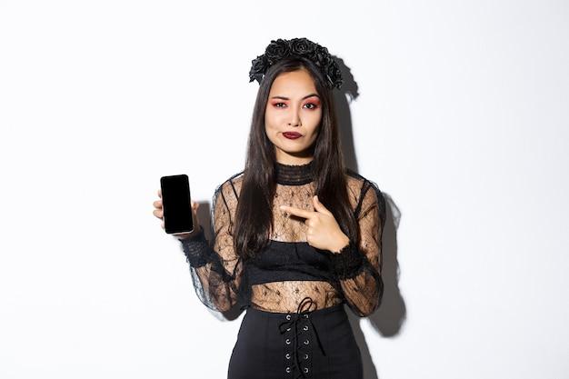 Sceptyczna atrakcyjna azjatka w czarnej eleganckiej koronkowej sukience i wieńcu uśmiecha się niezadowolony, wskazując palcem na telefon komórkowy, pokazując zły produkt, oceniając coś negatywnego.