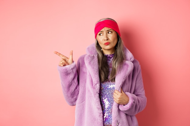 Sceptyczna azjatka w średnim wieku w fioletowym futrze patrząc i wskazując palcem w lewo z niezadowolonym, smutnym wyrazem twarzy, stojąca na różu.
