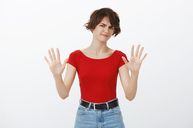 Sceptyczna i niechętna kobieta podnosząca ręce w odmowie, odmawia przyjęcia oferty