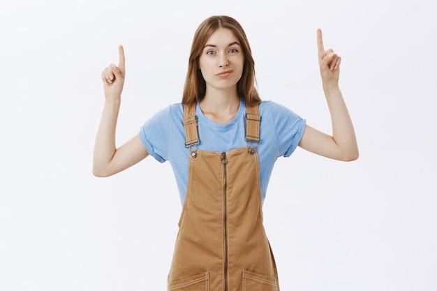 Sceptyczna i niezadowolona dziewczyna wskazuje palcem w górę na logo lub reklamę