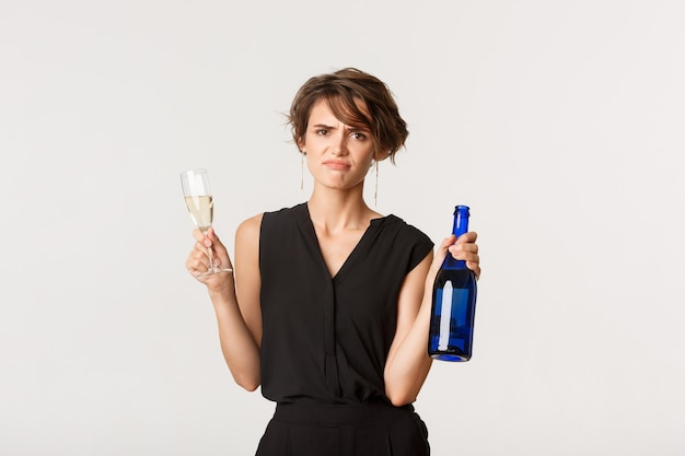 Sceptyczna i niezadowolona młoda kobieta, krzywiąca się zdenerwowana, trzymająca butelkę i kieliszek szampana, stojąca nad białym.