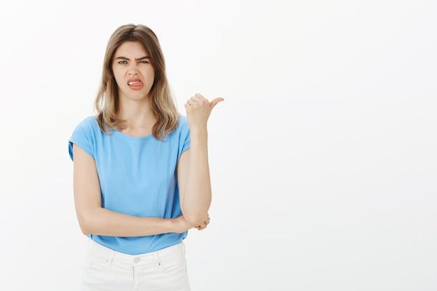 Sceptyczna i rozczarowana blondyneczka narzeka, wskazując palcem na coś niepokojącego lub złego