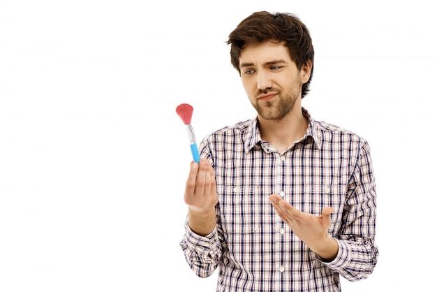 Sceptyczny chłopak wskazuje pędzel do makijażu