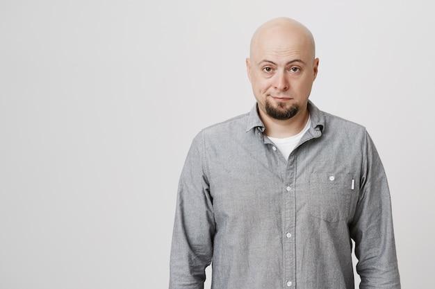 Sceptyczny i niechętny łysy mężczyzna patrzy z irytacją
