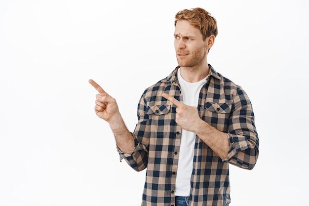 Sceptyczny i niezadowolony dorosły mężczyzna o rudych włosach, wskazujący i patrzący w lewo oceniający, marszczący brwi, patrząc na coś śmiesznego lub głupiego, stojący pod białą ścianą