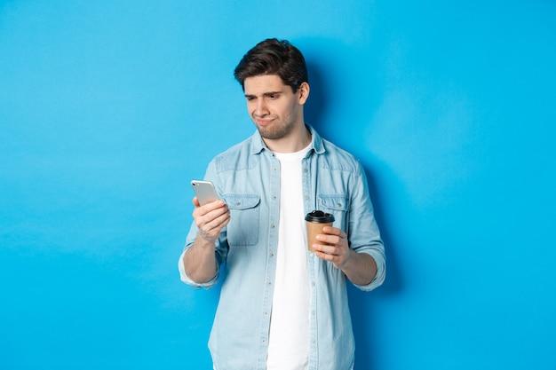 Sceptyczny i rozczarowany facet czytający smutną wiadomość w telefonie, trzymający filiżankę kawy, stojący nad niebieską ścianą