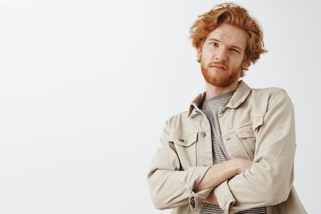 Sceptyczny i wątpliwy brodaty rudy facet pozuje pod białą ścianą