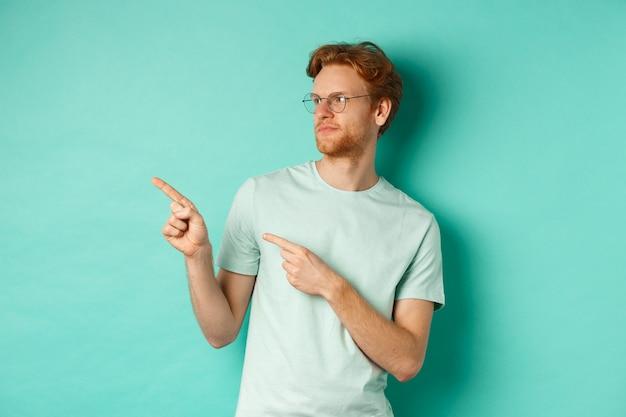 Sceptyczny kaukaski facet z rudymi włosami i brodą, w okularach i t-shircie, patrząc i wskazując na lewo rozczarowany, oceniając coś złego, stojąc na miętowym tle.