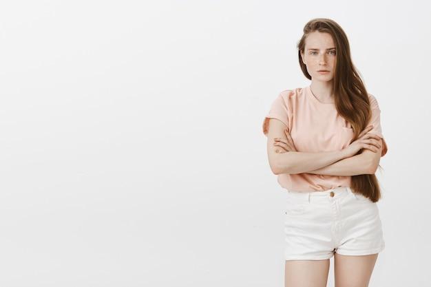 Sceptyczny nastolatka pozuje na białej ścianie