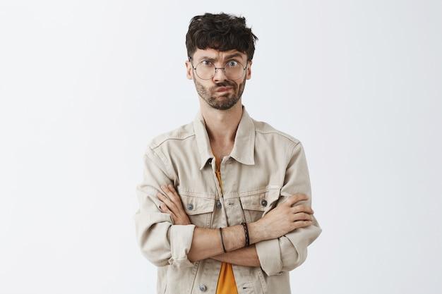 Sceptyczny stylowy brodaty facet pozuje przy białej ścianie
