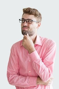 Sceptyk młody człowiek trzyma rękę na brodzie